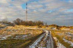 Ajardine com a estrada secundária que conduz à torre de rádio celular na área rural ucraniana Foto de Stock