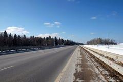 Ajardine com a estrada suburbana com metal uma cerca nos lados e a floresta sob o céu azul no dia de inverno ensolarado Imagem de Stock