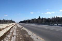 Ajardine com a estrada suburbana com metal uma cerca nos lados e a floresta sob o céu azul no dia ensolarado Imagem de Stock Royalty Free