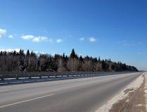 Ajardine com a estrada suburbana vazia com metal uma cerca nos lados e a floresta sob o céu azul no dia de inverno ensolarado Imagens de Stock Royalty Free