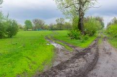 Ajardine com a estrada suja na área ucraniana rural na estação de mola Foto de Stock