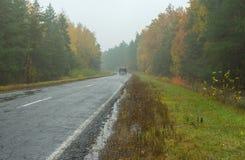 Ajardine com estrada, tempo chuvoso e transporte de motor só Imagem de Stock Royalty Free