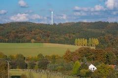 Ajardine com floresta, casas, árvores e roda de vento Foto de Stock