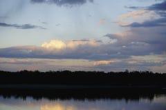 Ajardine com a floresta e as nuvens azuis do por do sol surpreendente refletidas no rio Dnieper, Kiev, Ucrânia Fotografia de Stock