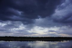 Ajardine com a floresta e as nuvens azuis do por do sol surpreendente refletidas no rio Dnieper, Kiev, Ucrânia Imagem de Stock Royalty Free