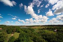 Ajardine com floresta, lago e céu com nuvens Foto de Stock