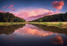 Ajardine com floresta, lago e nuvens no crepúsculo Imagem de Stock Royalty Free