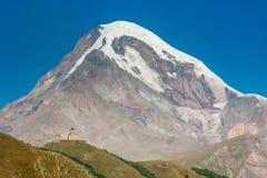 Ajardine com a igreja de trindade de Gergeti e monte Kazbek em Geórgia Fotografia de Stock Royalty Free