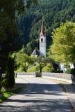 Ajardine com a igreja em Lutago, cumes sul de Tirol, Itália Imagem de Stock