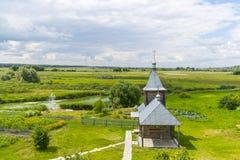 Ajardine com a igreja ortodoxa do russo e o céu nebuloso Russi Imagem de Stock Royalty Free