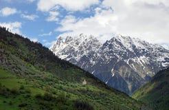 Ajardine com igreja ortodoxa em um montanhês em um fundo de montanhas neve-tampadas em Mestia Fotografia de Stock