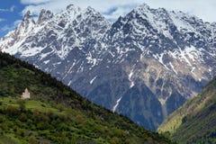Ajardine com igreja ortodoxa em um montanhês em um fundo de montanhas neve-tampadas em Mestia Foto de Stock Royalty Free