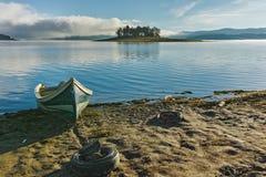 Ajardine com a ilha com pinhos e barco no reservatório de Batak, Bulgária Fotografia de Stock