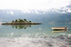 Ajardine com ilha rochosa e barco em um fiorde, com nuvens da manhã e reflexão na água, Noruega Fotos de Stock Royalty Free