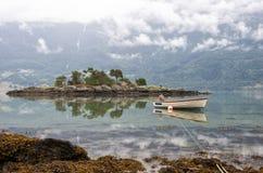 Ajardine com ilha rochosa e barco em um fiorde, em nuvens da manhã e em reflexão na água, Noruega Imagem de Stock