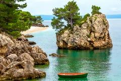Ajardine com ilha rochosa e três na praia Fotografia de Stock Royalty Free