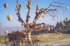 Ajardine com jarros em uma árvore e em um vagão velho completamente de potenciômetros de argila Fotos de Stock Royalty Free
