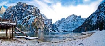 Ajardine com lago da montanha, as montanhas nevado, o céu azul e a madeira Imagens de Stock
