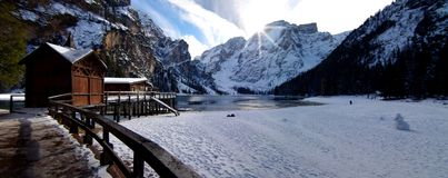 Ajardine com lago da montanha, as montanhas nevado, o céu azul e a madeira Foto de Stock Royalty Free
