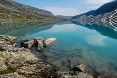 Ajardine com lago de turquesa, pedras e montanhas, Noruega Fotografia de Stock Royalty Free