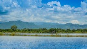 Ajardine com lago e montanha no céu azul do dia Fotografia de Stock Royalty Free