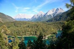 Ajardine com lago e os cumes bávaros no fundo Fotografia de Stock Royalty Free