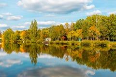 Ajardine com lago, o céu nebuloso, e as árvores refletidas simetricamente na água Lago salt Sosto Nyiregyhaza, Hungria imagem de stock