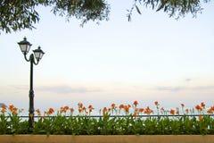 Ajardine com latern, o mar, as flores e a grama Imagens de Stock Royalty Free