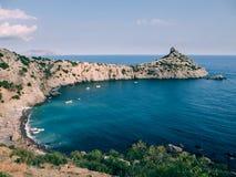 Ajardine com mar e montanhas e a praia sob céus azuis Foto de Stock Royalty Free