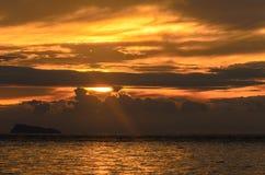 Ajardine com mar e nebuloso sob o céu com por do sol no e Fotos de Stock