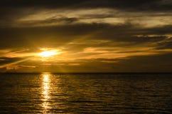 Ajardine com mar e nebuloso sob o céu com por do sol no e Fotografia de Stock