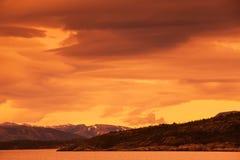 Ajardine com mar e o céu tormentoso dramático vermelho Fotografia de Stock