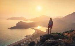 Ajardine com menina, mar, cumes da montanha e o céu alaranjado Fotografia de Stock