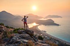 Ajardine com menina, mar, cumes da montanha e o céu alaranjado Foto de Stock