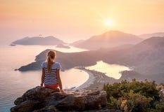 Ajardine com menina, mar, montanhas e o céu alaranjado Fotos de Stock