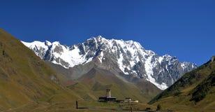 Ajardine com a montanha de Cáucaso Shkhara vista da casa de campo de Ushguli Imagens de Stock Royalty Free