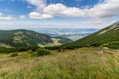 Ajardine com montanha e as nuvens agradáveis em Krkonose na república checa Imagem de Stock