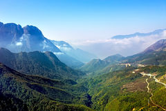 Ajardine com montanha, nuvens, e o céu azul Fotos de Stock Royalty Free