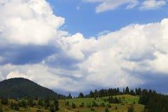 Ajardine com montanhas, as nuvens brancas e o céu azul Fotos de Stock Royalty Free