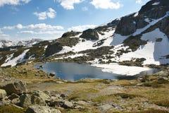 Ajardine com montanhas e neve em um dia ensolarado Foto de Stock Royalty Free