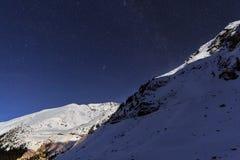 Ajardine com montanhas e o céu azul na noite do inverno Fotografia de Stock Royalty Free