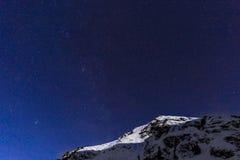 Ajardine com montanhas e o céu azul na noite do inverno Foto de Stock