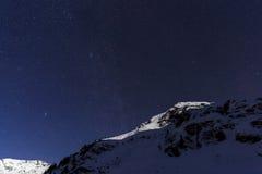 Ajardine com montanhas e o céu azul na noite do inverno Fotos de Stock Royalty Free