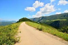 Ajardine com montanhas, estrada e o céu azul Foto de Stock
