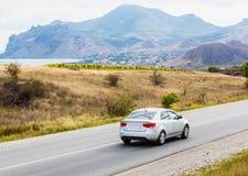 ajardine com montanhas, lago, estrada e carro Imagem de Stock