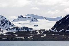 Ajardine com montanhas nevado em um dia ensolarado visto do mar Imagens de Stock