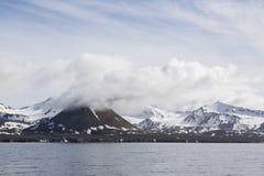 Ajardine com montanhas nevado em um dia ensolarado visto do mar Foto de Stock Royalty Free