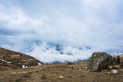 Ajardine com montanhas nevado, nuvens fechados, Nepal Foto de Stock
