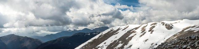 Ajardine com montanhas, neve e o céu azul Foto de Stock