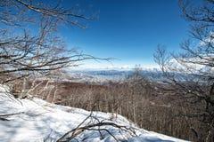 Ajardine com montanhas, neve e o céu azul Imagem de Stock